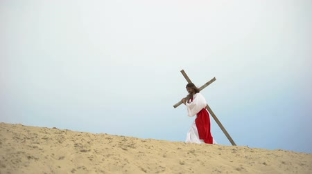 crucifixo : Jesus falling under heavy wooden cross, suffering pain and exhaustion, sacrifice