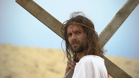 crucified : Jesus turning bloody head with crown of thorns to camera, carrying heavy cross