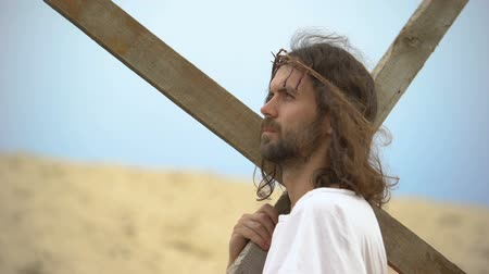 crucifixo : Jesus Christ with crown of thorns carrying cross, praying to God for sinners Stock Footage
