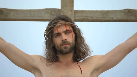 crucified : Jesus suffering nailed to cross, looking into camera, sacrifice for sinners
