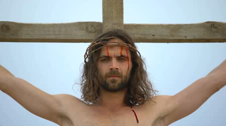simbolismo : Jesus nailed to cross looking to sky, blood drops flowing down face, crucifixion