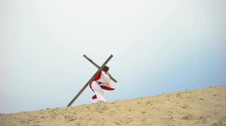 crucifixo : Jesus with heavy wooden cross hardly walking, biblical story of crucifixion Stock Footage