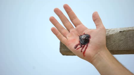 symbolismus : Jesus hand nailed to cross, clotted blood on wound, reenactment of crucifixion