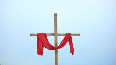 acreditar : Wooden cross with red cloth wrapped around, crucifix and resurrection of Jesus