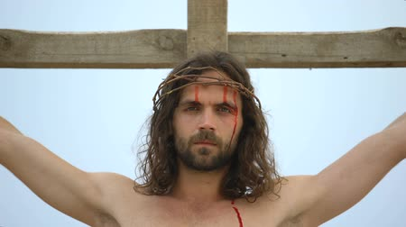 simbolismo : Exhausted Jesus nailed to cross, looking into camera, atoning humanity sins