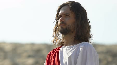 благодать : Jesus Christ in robe and sash observing desert, searching for oasis, close-up