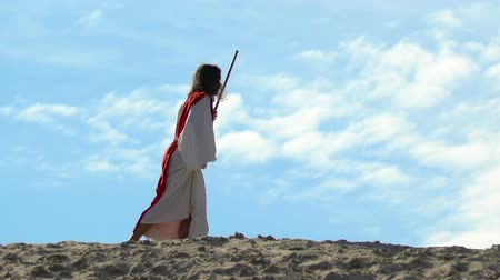 pap : Tired Jesus with staff in robe and sash hardly walking through sandy hills Stock mozgókép