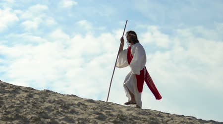pap : Exhausted Jesus with staff in robe and sash walking through desert, religion Stock mozgókép