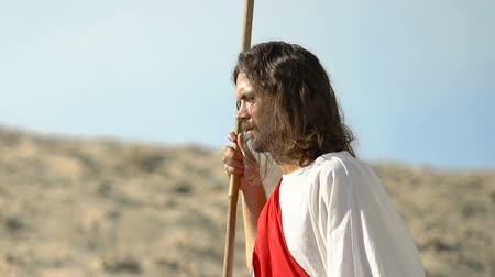 священник : Jesus with stuff in robe looking at desert and smiling after long road, close-up