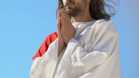 sinner : Jesus Christ in robe praying outdoors, blessing God, Christian religion concept Stock Footage