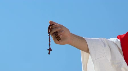 экономить : Hand of priest raising rosary to heaven, blessing God and praying, close-up