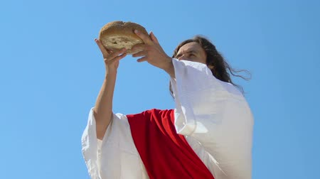 holy heaven : Jesus in robe and sash raising bread to heaven, asking God for blessing food Stock Footage