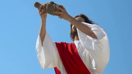 geçen : Jesus Christ in robe raising bottle to heaven, asking God for blessing water