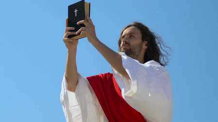 duch Święty : Jesus Christ in robe and sash raising Holy Bible to heaven, praying God, preach
