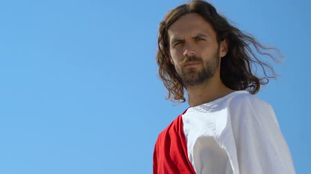 евангелие : Peaceful Jesus Christ in robe looking into camera against sky background