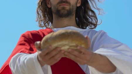 holy heaven : Saint Jesus in robe stretching bread into camera, gifts for poor people, charity