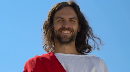 благодать : Extremely happy Jesus looking at camera against sky background, saving soul