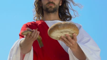святой : Saint Jesus Christ in robe stretching fish and bread into camera, son of God