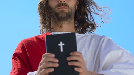 священник : Jesus in robe showing Holy Bible at camera, faith and belief concept, religion