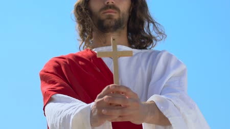 crucifixo : Jesus in robe showing wooden cross at camera, Christian religion symbol, closeup
