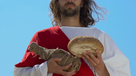 holy heaven : Jesus in robe and sash holding bottle of wine and bread, gifts from heaven Stock Footage