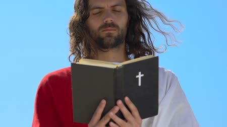 crucifixo : Jesus in robe reading Holy Bible and praying God with eyes closed, religion Stock Footage