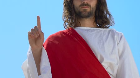 forefinger : Jesus in robe raising forefinger to heaven, preaching word of God, Christianity Stock Footage