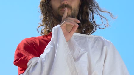 экономить : Jesus Christ in robe showing silence sign, patience and forgiveness concept