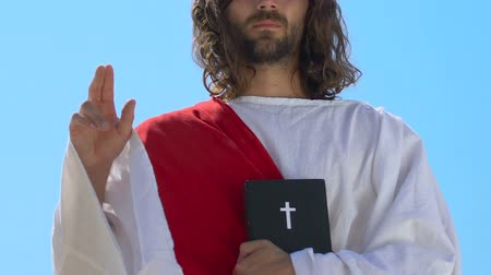 священник : Jesus showing benediction sign, holding Bible, Papal blessing hand gesture