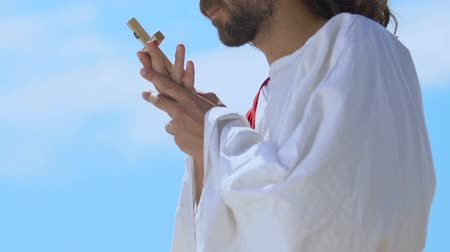 アピール : Holy man with closed eyes kissing cross, praying God for soul salvation devotion