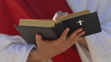 mensen massa : Priest reading Bible celebrating mass, preaching Christian religion, closeup Stockvideo