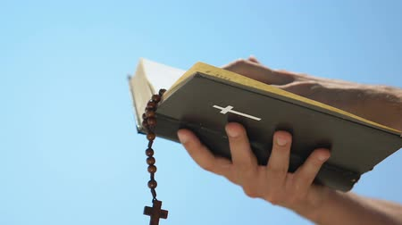 evangelical : Male hands holding bible with rosary, priest praying celebrating mass, baptism Stock Footage