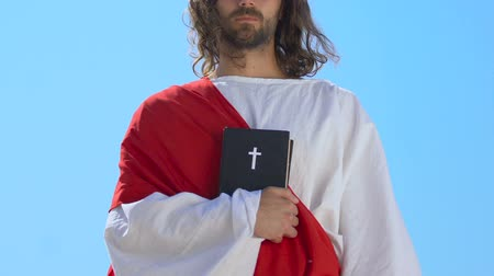 crucifixo : Jesus in robe and sash holding holy bible near heart against sky background Stock Footage