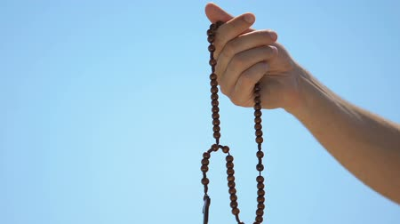 ziel : Man holding rosary praying to god on sky background, atonement for sin, closeup