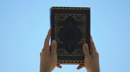redemption : Hands raising Koran praying , spread of sacred Islamic teachings, theology