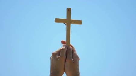 bem aventurança : Hands holding cross against sky background, christian baptism, spirituality