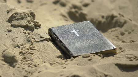 redemption : Holy Bible abandoned in sand, forgotten ancient knowledge, old rejected religion Stock Footage