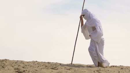 metaphors : Tired traveler in muslim clothes falling on sand, life difficulties, hard road