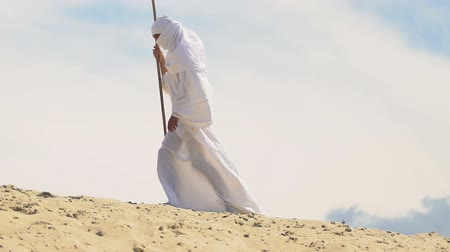 театральный : Man wearing muslim clothes walking in hot desert, threat of fatigue, dehydration Стоковые видеозаписи
