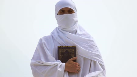 testament : Muslim with hidden face hugging Koran tightly, radical Islamic faith, shariah