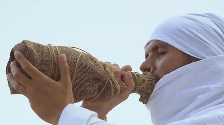 sucho : Thirsty traveler in muslim clothing drinking water, dehydration in desert