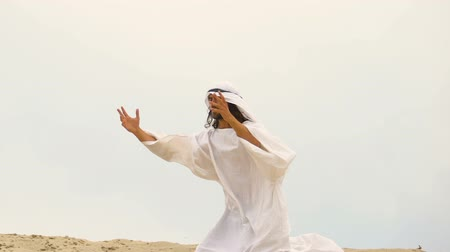 ajoelhado : Muslim falls to knees in desert, raising hands praying  for forgiveness