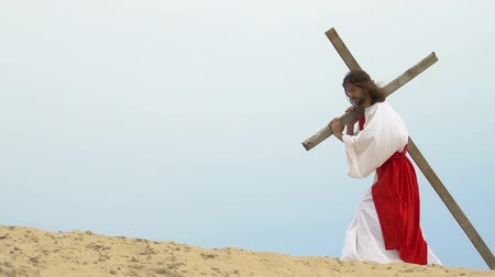 crucified : Jesus falling with heavy cross, suffering on road to calvary Hill, crucifixion