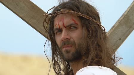 crucifixo : Christ with bloody head holding cross, looking into camera, sacred sacrifice