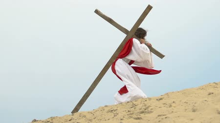 crucified : Exhausted Jesus carrying heavy wooden cross walking to Calvary hill, crucifixion