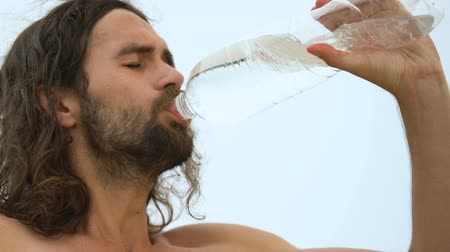 long hair : Thirsty man greedily drinking mineral water, dehydration in hot weather, closeup Stock Footage