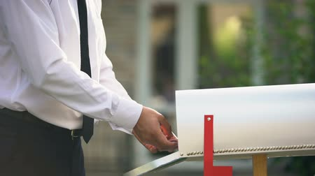 почтальон : Businessman sending letters and bills, putting them into mailbox near house