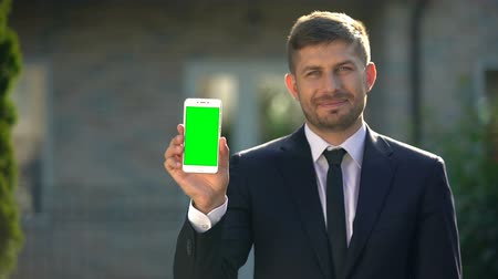 komisyoncu : Estate agent holding smartphone with green screen, app for housing rental Stok Video