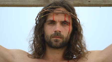 crucified : Portrait of Jesus crying and suffering nailed to cross, religious self-sacrifice