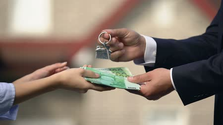 estate agency : Lady giving euro cash to broker and receiving keys from house, buying of housing